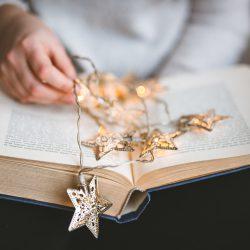 Fotografia de uma menina segurando um livro aberto sobre o qual estão luzes em formato de estrela.