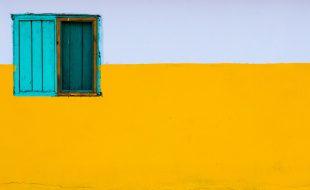 Janela de madeira azul sob fundo amarelo e branco