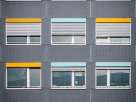 Fachada de prédio com janelas de diferentes cores.